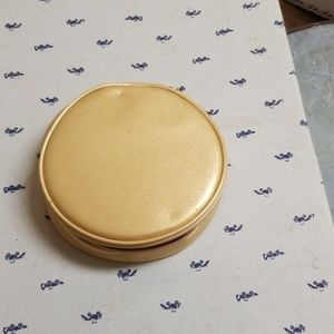 Round gold Estee Lauder makeup/jewelry pouch